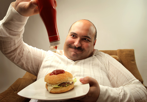 overweight-man-pouring-ketchup-on-a-hamburger