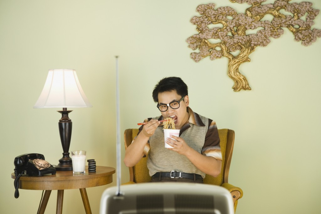 Nerdy Asian man eating in front of television