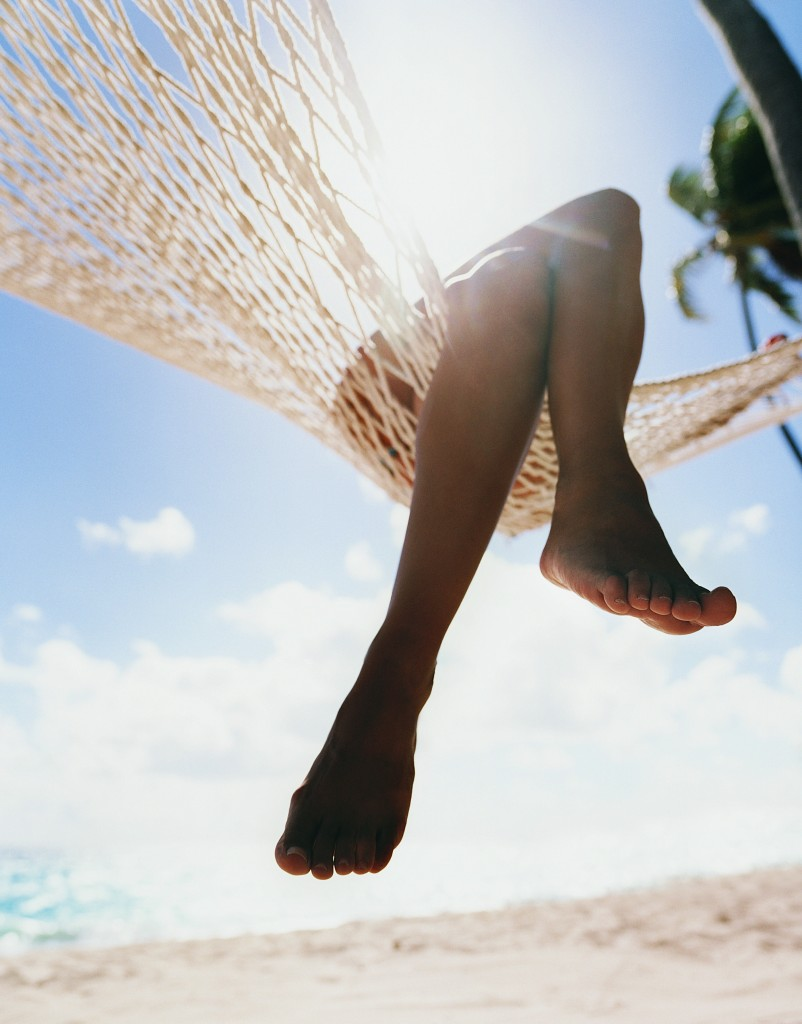 Close up of a Person's Crossed Legs Hanging at the Edge of a Hammock on a Beach